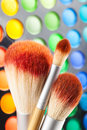 Makeup brushes and palette of colorful eye shadows as background Stock Images
