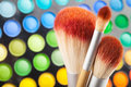 Makeup brushes and palette of colorful eye shadows as background Royalty Free Stock Photo