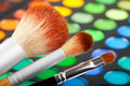 Makeup brushes and set of colorful eye shadows Royalty Free Stock Photos