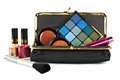 Makeup collection bag with assorted cosmetics over a white background Stock Photography
