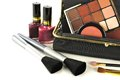 Makeup collection bag close up with assorted cosmetics over a white background Royalty Free Stock Photography