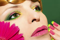 Makeup and nails with gerberas beautiful colorful on a young girl on a green background close up Stock Photo