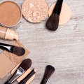 Makeup products to even out skin tone and complexion frame accessories laid as on shabby wooden surface concealer pencil Stock Photography
