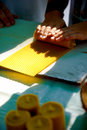 Making candle from honey bee wax plate at market. Royalty Free Stock Photo
