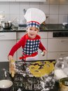 Making cookies photo of an adorable boy in a chef hat and apron in the kitchen Royalty Free Stock Images