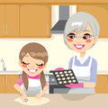 Making cookies together little girl and grandmother star shaped gingerbread in house kitchen Stock Image