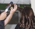 Making curles with hair iron at the hairdressers Royalty Free Stock Photo