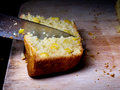 Making the cut cutting corn bread with knife on chopping board Royalty Free Stock Photos
