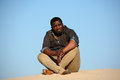 Making decisions african american young man with bothered facial expression sitting in the sand thinking Royalty Free Stock Photography