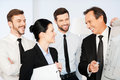We are making great progress confident mature businessman pointing graph on whiteboard and smiling while his colleagues standing Stock Image