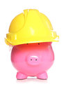 Making money from property construction piggy bank wearing a hard hat cutout Stock Images