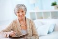 Making notes portrait of aged female with notepad looking at camera with smile Stock Image