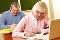 Making notes portrait of mature female in copybook with senior men on background Royalty Free Stock Photos