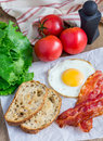 Making open face sandwich with egg bacon tomato and lettuce Stock Images