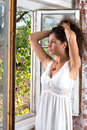 Making a ponytail long haired woman in lingerie looking out of the window Royalty Free Stock Image