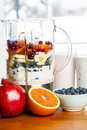 Making smoothies in blender with fruit and yogurt prepared healthy smoothie ingredients fresh ready to blend on kitchen table Royalty Free Stock Photo