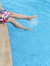Making splashes female feet in the pool Stock Photos