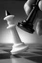 Making a strategic move conceptual image depicting with hand moving chess piece on chessboard during game of skill Royalty Free Stock Photo