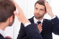 Making sure he looks perfect handsome young man in formalwear adjusting his hairstyle and smiling while standing against mirror Stock Image