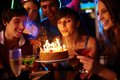 Making a wish portrait of charming girl blowing on candles on birthday cake surrounded by friends at party Stock Images