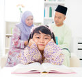 Malay girl reading book southeast asian family at home muslim parents and child living lifestyle Stock Photography