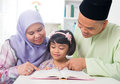 Malay muslim family reading a book parents teaching child southeast asian at home Royalty Free Stock Images