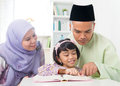 Malay muslim parents teaching child reading a book southeast asian family at home Stock Photos