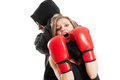 Male aggressor grabbing a frightened woman wearing boxing gloves women female victim concept on white background Stock Photography
