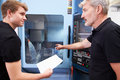 Male apprentice working with engineer on cnc machinery Royalty Free Stock Image