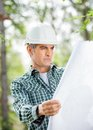 Male architect analyzing blueprint at site mature construction Royalty Free Stock Photos