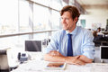 Male architect at his desk in an office, looking away Royalty Free Stock Photo