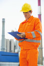 Male architect in protective workwear writing on clipboard at site Stock Photography