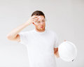 Male architect in safety glasses taking off helmet picture of Royalty Free Stock Photography