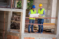 Male architects look at blue print on building construction Royalty Free Stock Photo