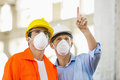 Male architects wearing protective mask while working at construction site Royalty Free Stock Images