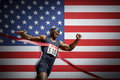 Male athlete crossing finish line against American flag Royalty Free Stock Photo