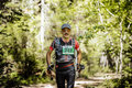 Male athlete midlife age runs in woods with nordic poles in hand Royalty Free Stock Photo