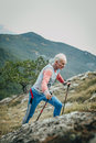 Male athlete senior years with walking sticks going uphill Royalty Free Stock Photo