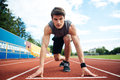 Male athlete about to start a sprint looking at camera Royalty Free Stock Photo