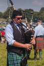 Male bagpipe player in record heat at the scottish games in the plains virginia a man walks through the crowds playing the Stock Photo