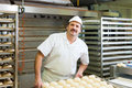 Male baker baking bread rolls fresh in the bakehouse Stock Image