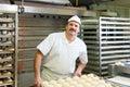 Male baker baking bread rolls fresh in the bakehouse Stock Image