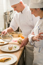 Male baker showing apprentice serving puff pastry female Stock Photo