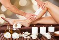 Male beautician waxing woman's leg in spa Royalty Free Stock Photo