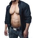 Male bodybuilder in jeans and open shirt revealing pecs and abs really muscular Royalty Free Stock Photo
