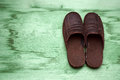 Male brown slippers lying on the wooden floor Royalty Free Stock Photo