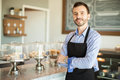 Male business owner in a bakery portrait of young wearing an apron and standing front of his cake shop Stock Photography