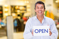 Male business owner holding an open sign and smiling Royalty Free Stock Images