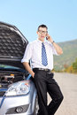 Male businessperson talking on phone on an open road next to a car Royalty Free Stock Image