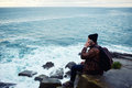 Male calling via cell telephone while enjoying beautiful sea landscape in cool autumn day